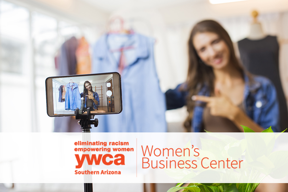 Woman holding up a shirt on a hanger while using her phone to record content with an overlay of the YWCA logo