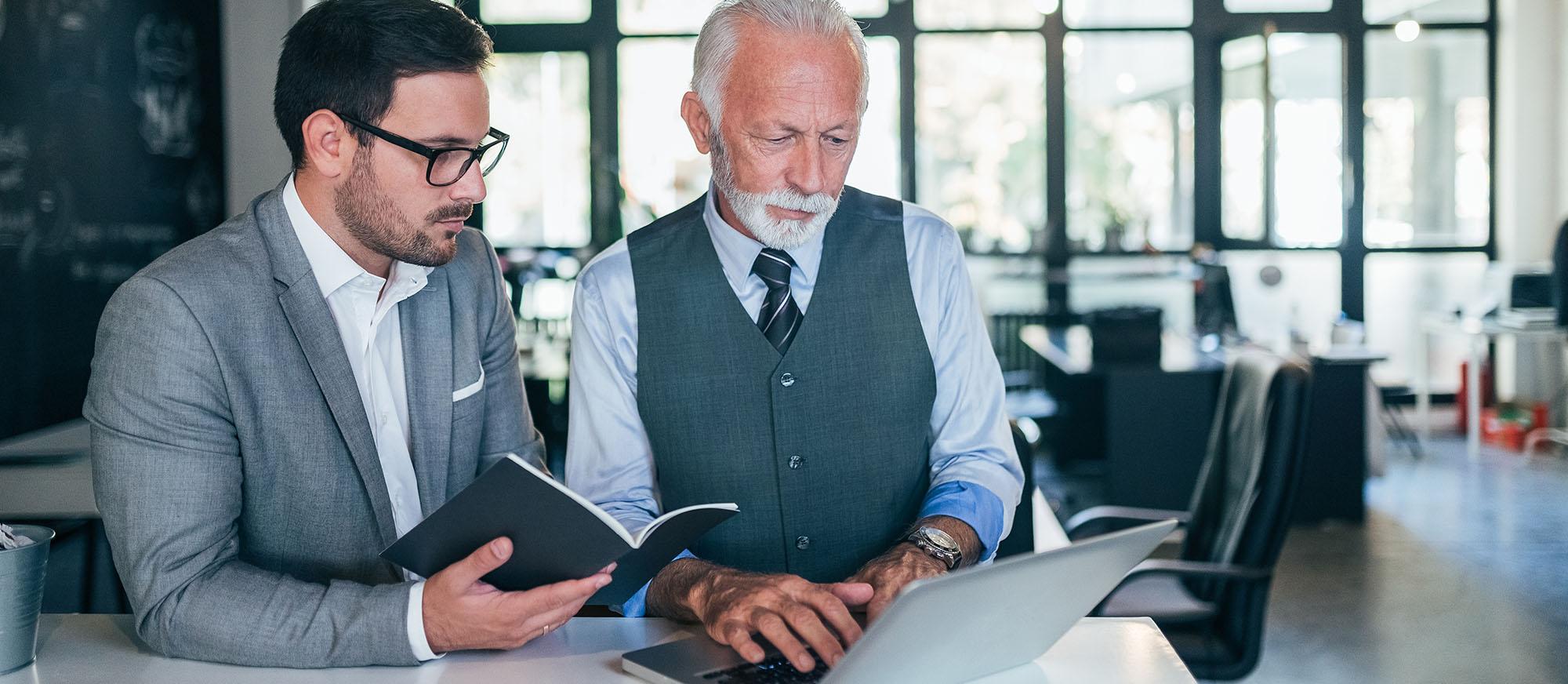 A mentor teaching their mentee at a desk
