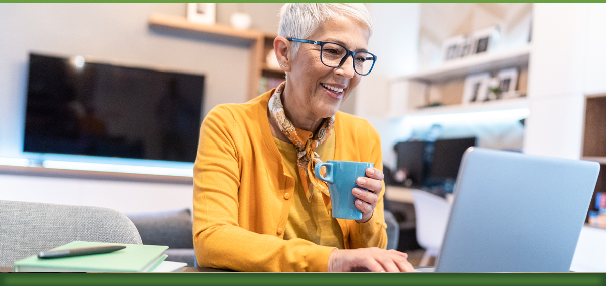 Woman wearing yellow shirt and glasses drinking coffee while on laptop
