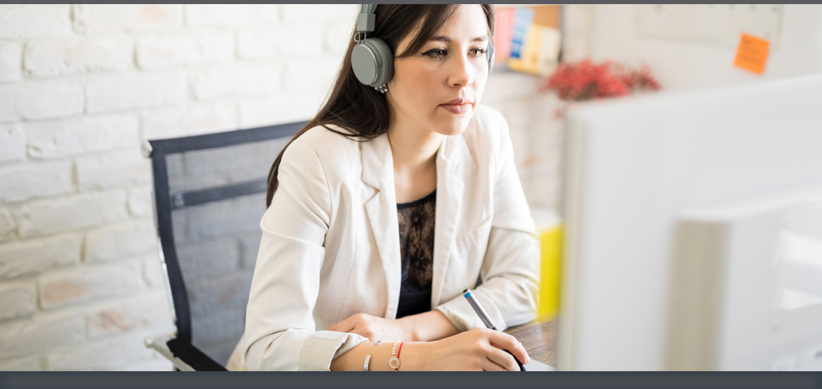 Woman with earphones on watching her laptop while she takes notes
