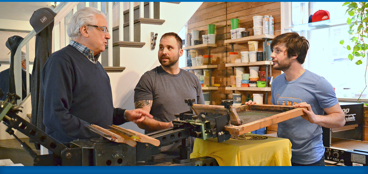Mentor giving advice to screen printing shop business owners