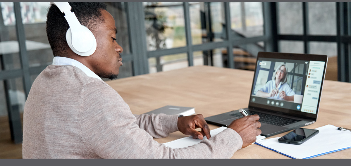 Man with earphones on watching his laptop while he takes notes