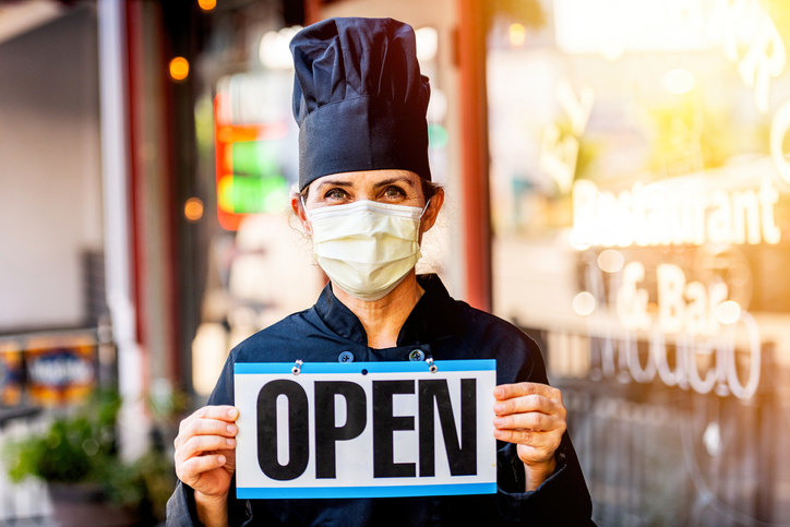 "Chef holding an ""open"" Sign"