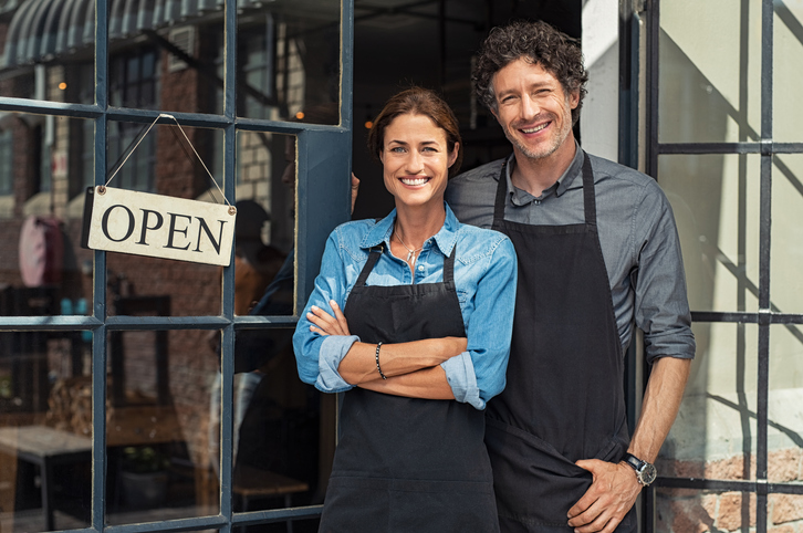 Smiling small business owners outside of their open business