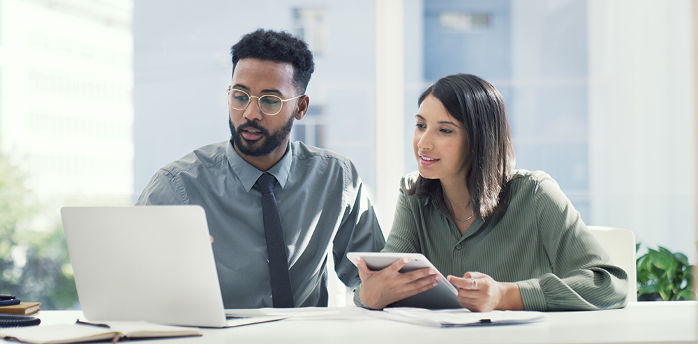 Woman and man in mentoring session looking at a laptop