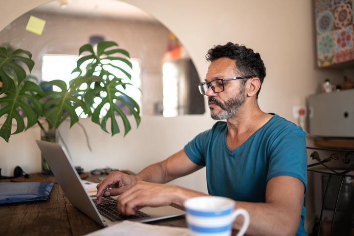 Hispanic man typing at his computer.