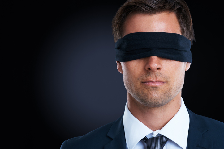Business man with a blind fold on