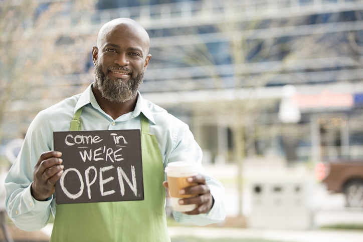 Proud business owner holding a cup of coffee and open sign