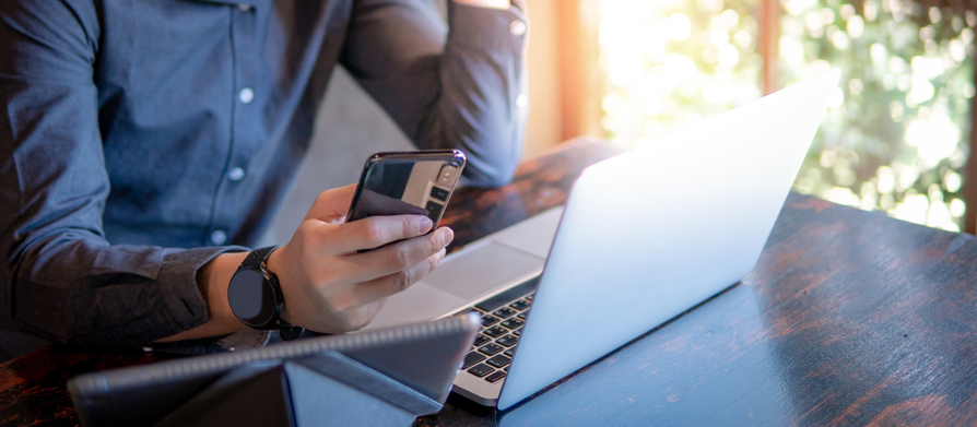 Businessman holding Smartphone in front of tablet and laptop