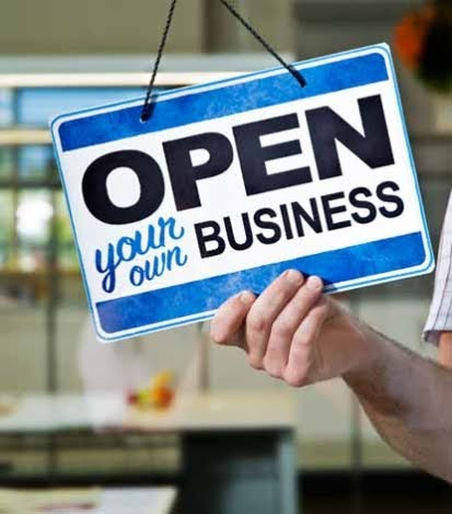 Photo of a store sign in a door that reads 'Open Your Own Business'