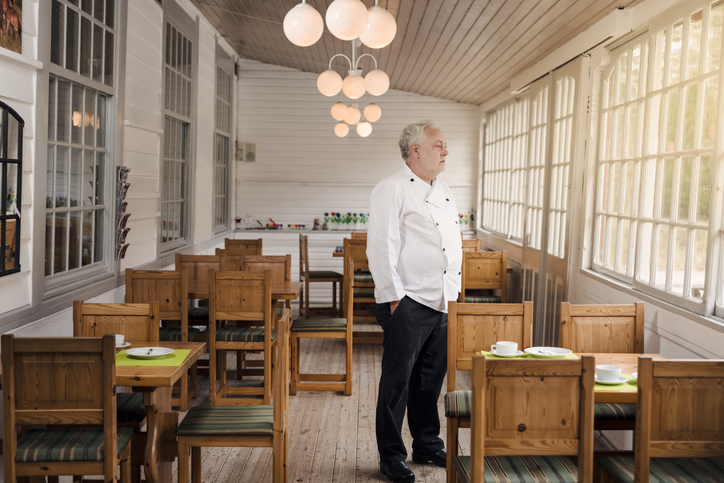 Restaurant owner in empty dining room looking out of window