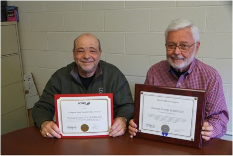 Sal Gambino, Treasurer and George Joiner, Chairman displaying Putnam SCORE's recently received SCORE awards