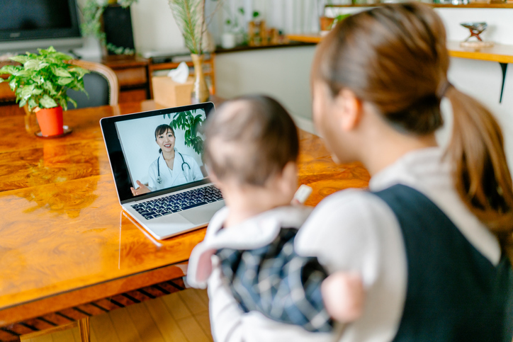 Women and baby video conferencing with doctor