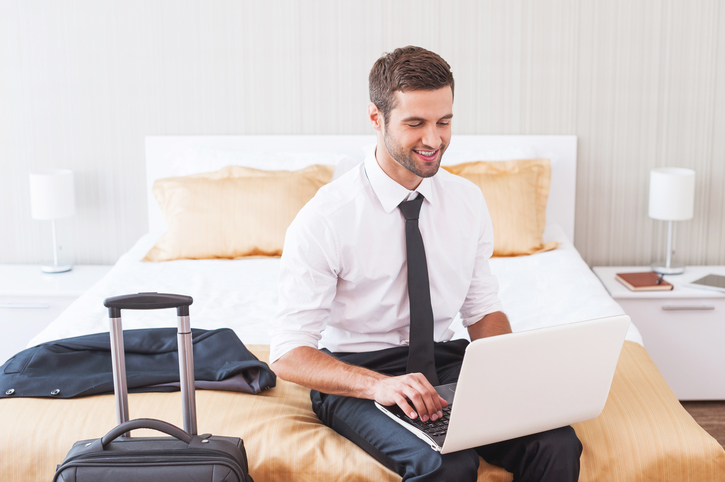 business man works on laptop in hotel room