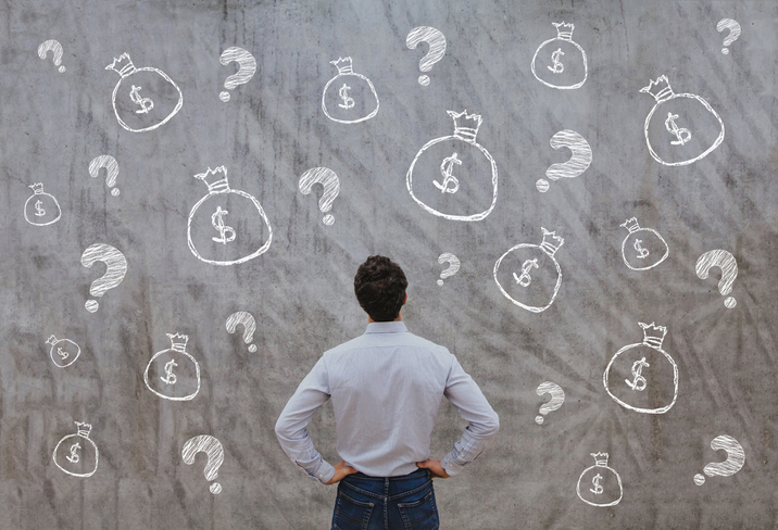 man looking at chalkboard with money bags and question marks