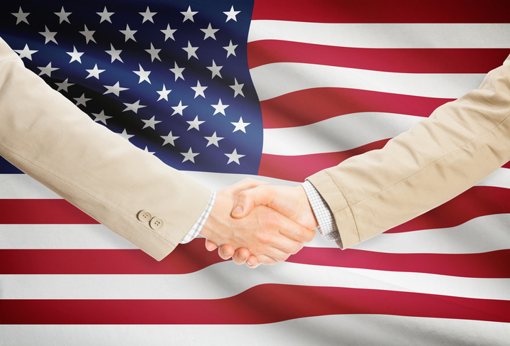 handshake in front of flag