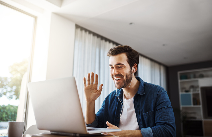 Happy employee waving at co-worker on laptop screen