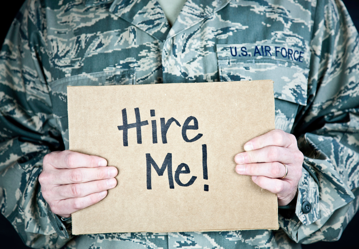 veteran holding hire me sign
