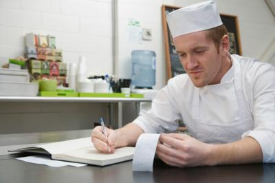 Chef looking at receipts and recording in notebook
