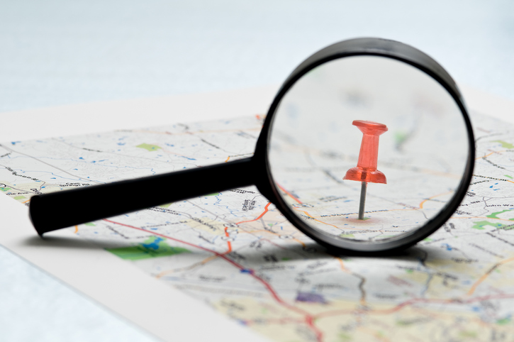 magnifying glass on pushpin on map