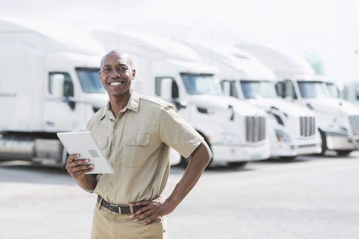man in front of fleet of trucks