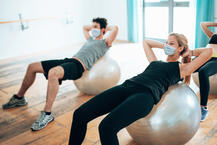 man and woman on exercise balls in gym wearing masks