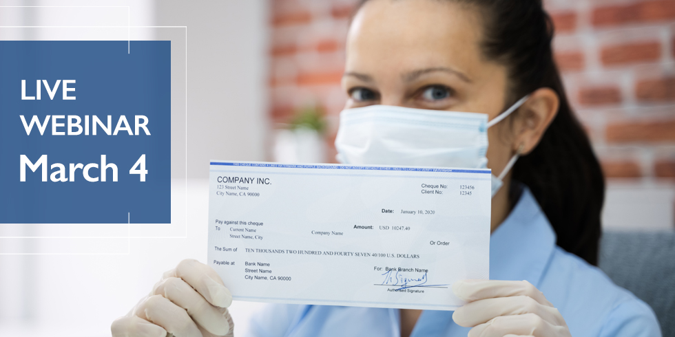 Woman wearing a mask and gloves holding up a check