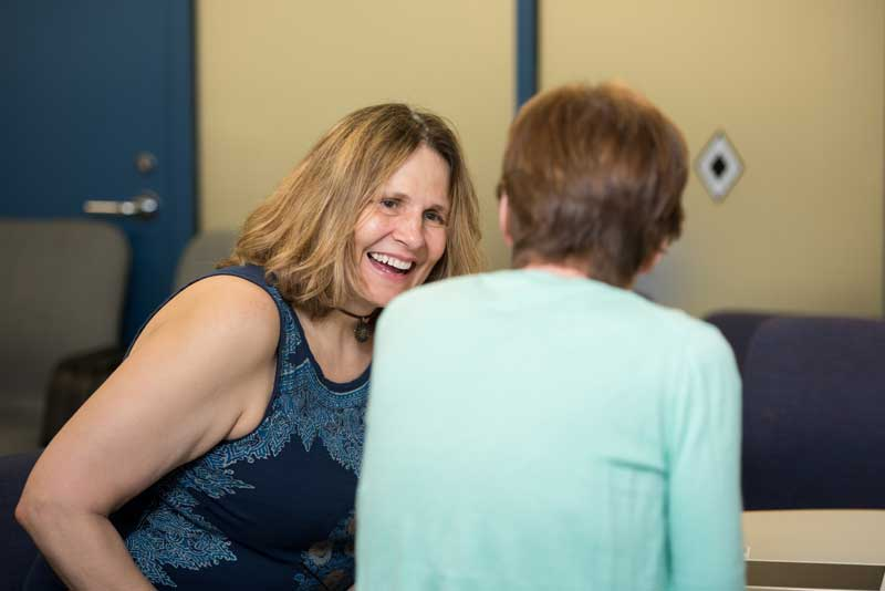 Woman smiling while speaking with mentor