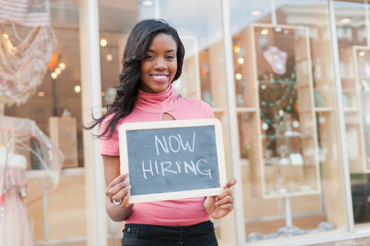 woman holding now hiring sign