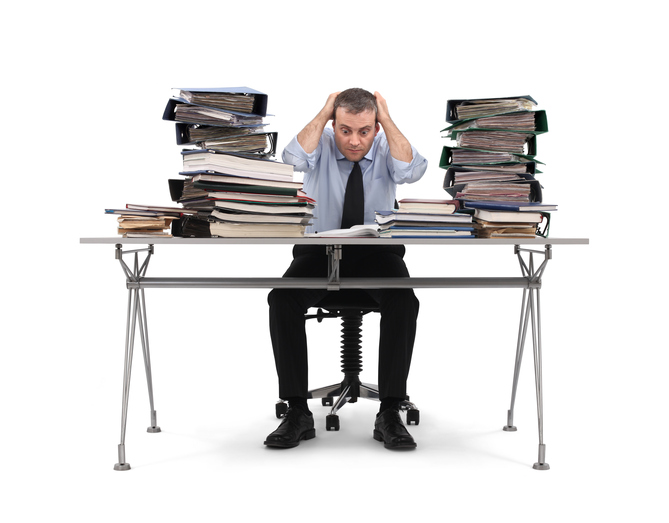 overwhelmed businessman at a messy desk