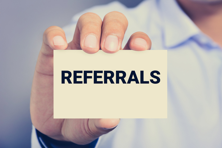 man holding card referrals