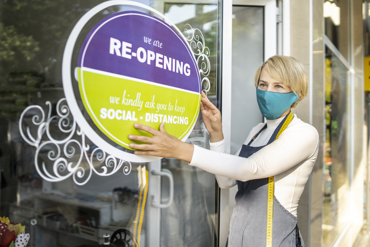 woman wearing mask putting sign on store about reopening after covid