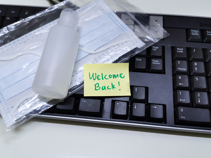 black keyboard with hand sanitizer and yellow sticky note saying welcome back