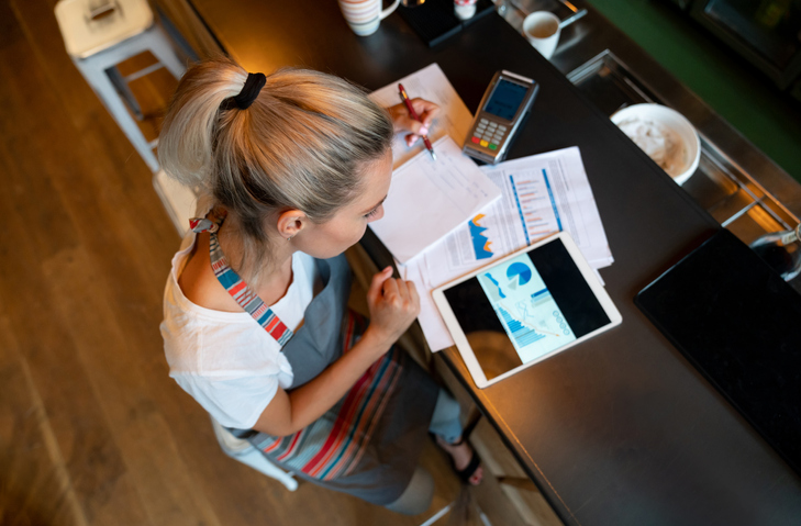 blonde woman wearing apron sitting at bar with hair in ponytail with calculator and business documents