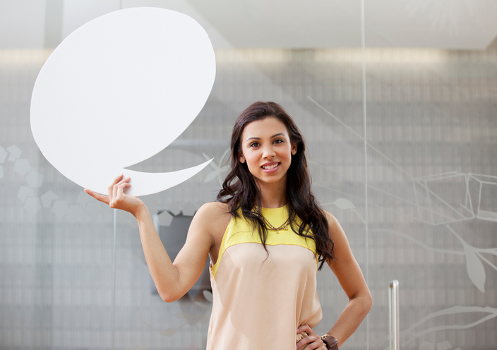 woman holding speech bubble sign