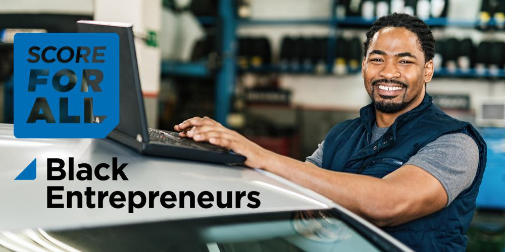 Black man business owner in garage on laptop