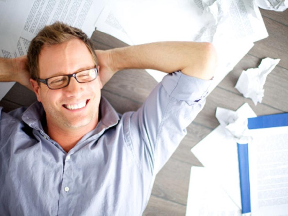 man smiling and laying in relaxed position