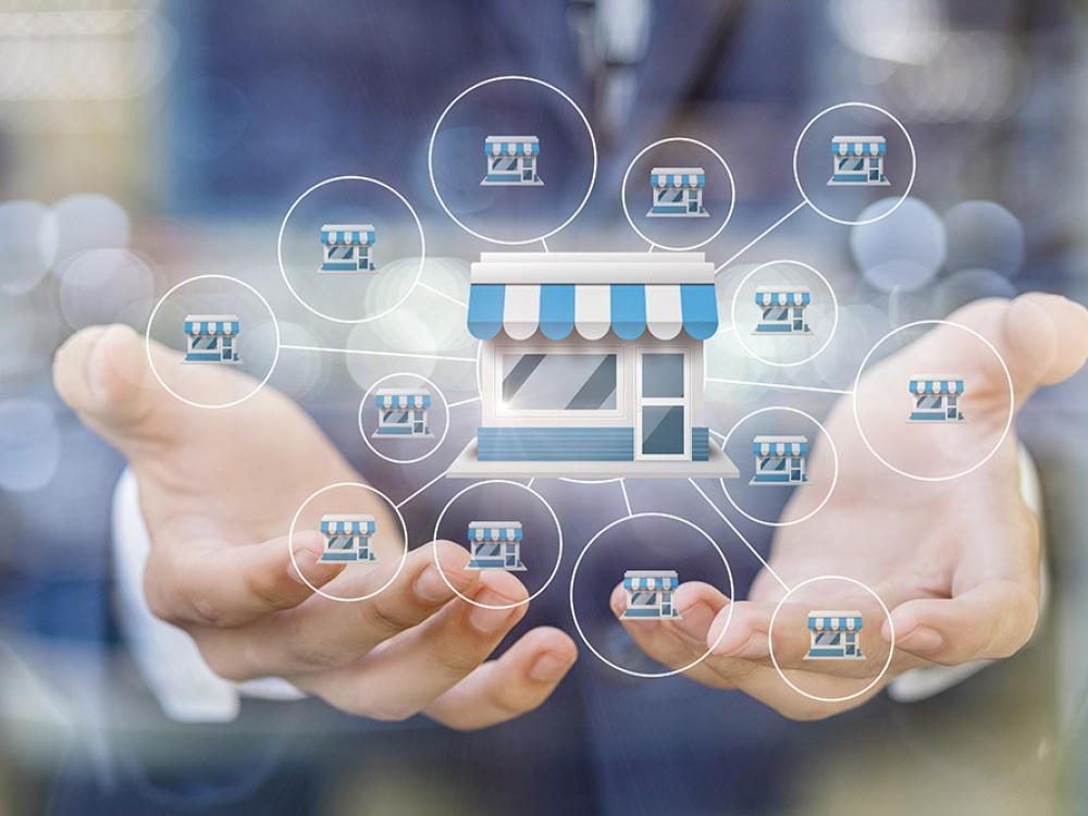 man with hands together holding images of store front icons that are connected