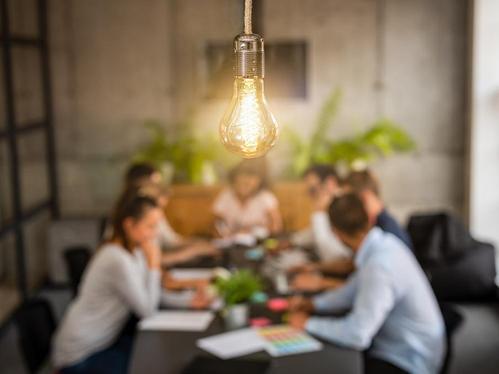lightbulb with people meeting in background
