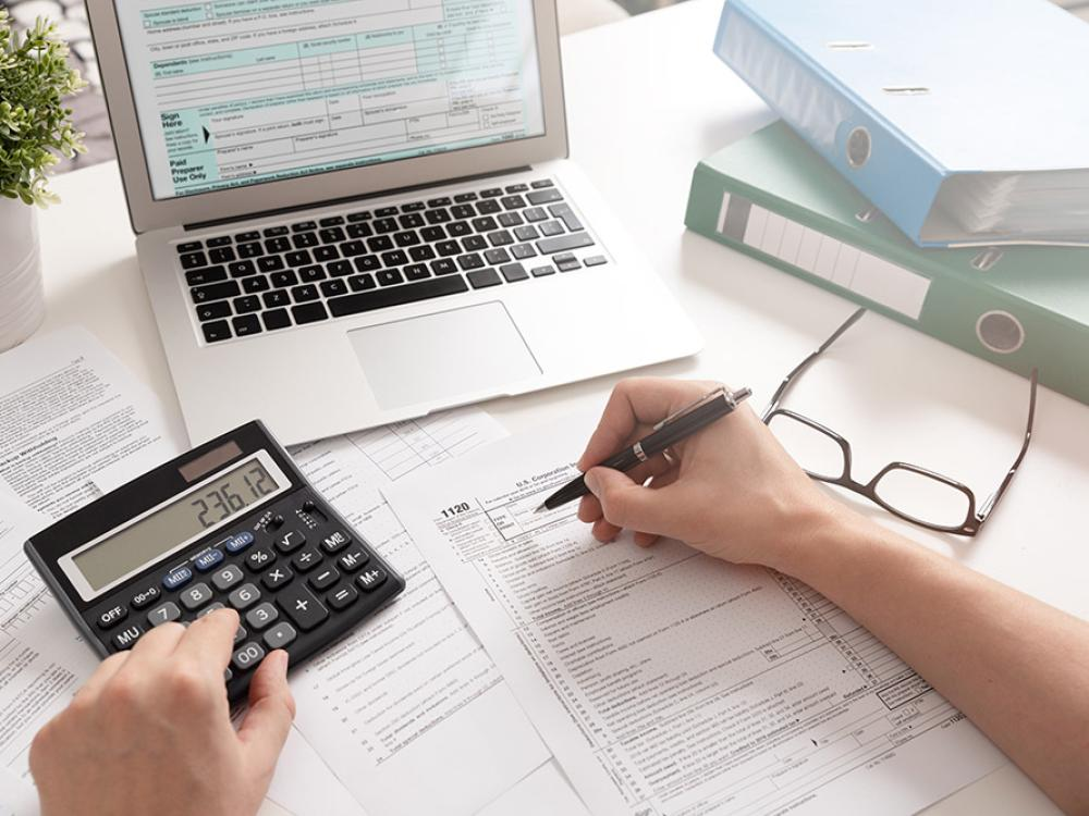 Business owner at desk going over corporation taxes