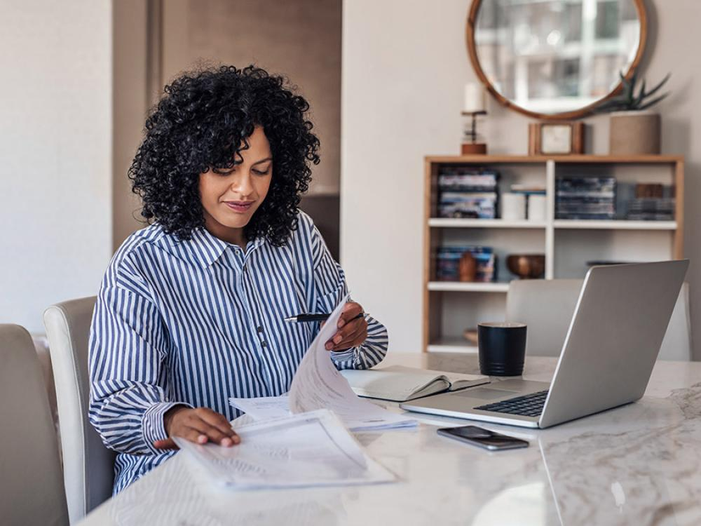 Woman on laptop working at her dining room table