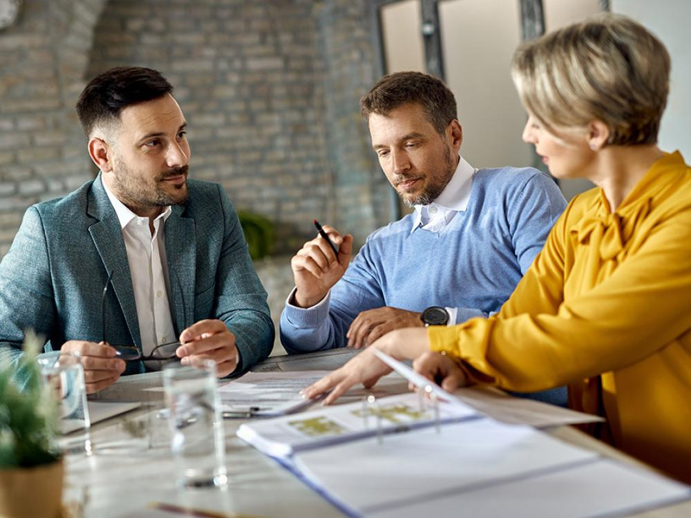 Three people having a meeting with documents on table