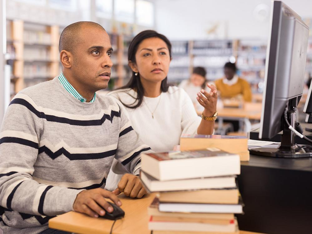 latin american man getting small business research assistance in a public library