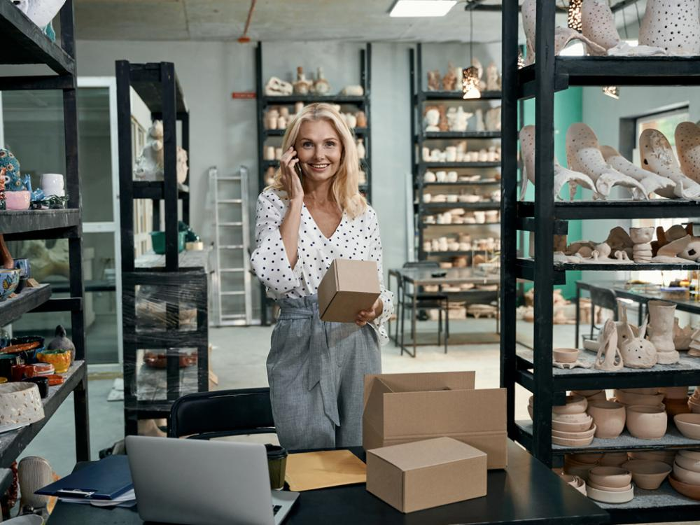 Cheerful woman, small business owner smiling at camera, talking on the phone, holding cardboard box while preparing order, standing in her craft pottery shop