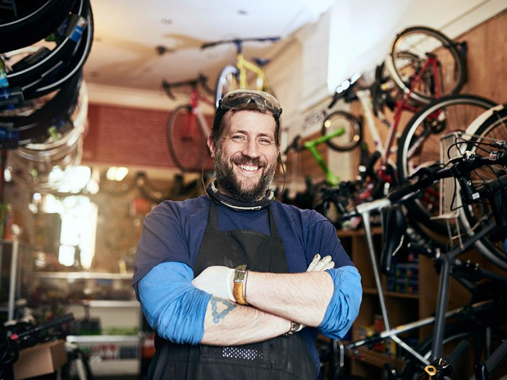 Man smiling in his bicycle shop