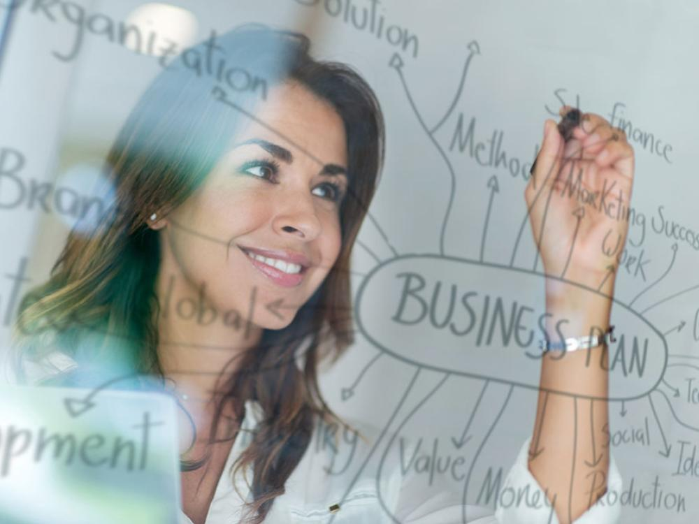 Woman writing business plan brainstorming on clear glass board