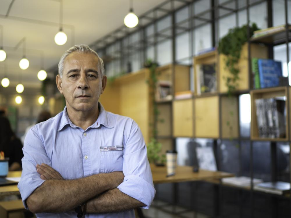 older hispanic gentleman standing outside business in apron