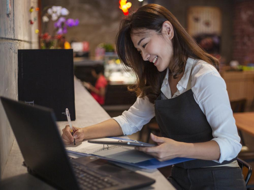 asian woman sits at bar with computer tablet and notebook