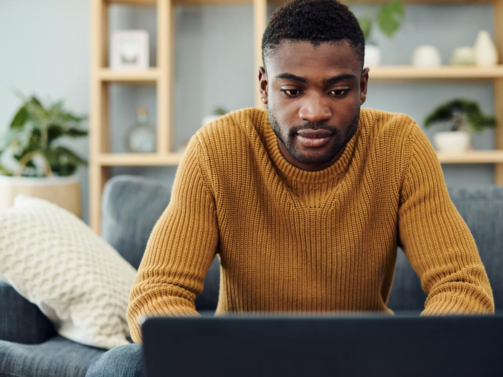 young black man in yellow sweater using laptop
