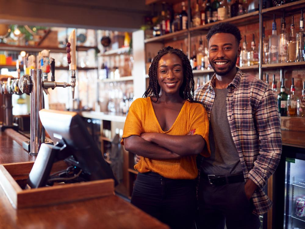 Black couple who owns bar standing behind the counter smiling